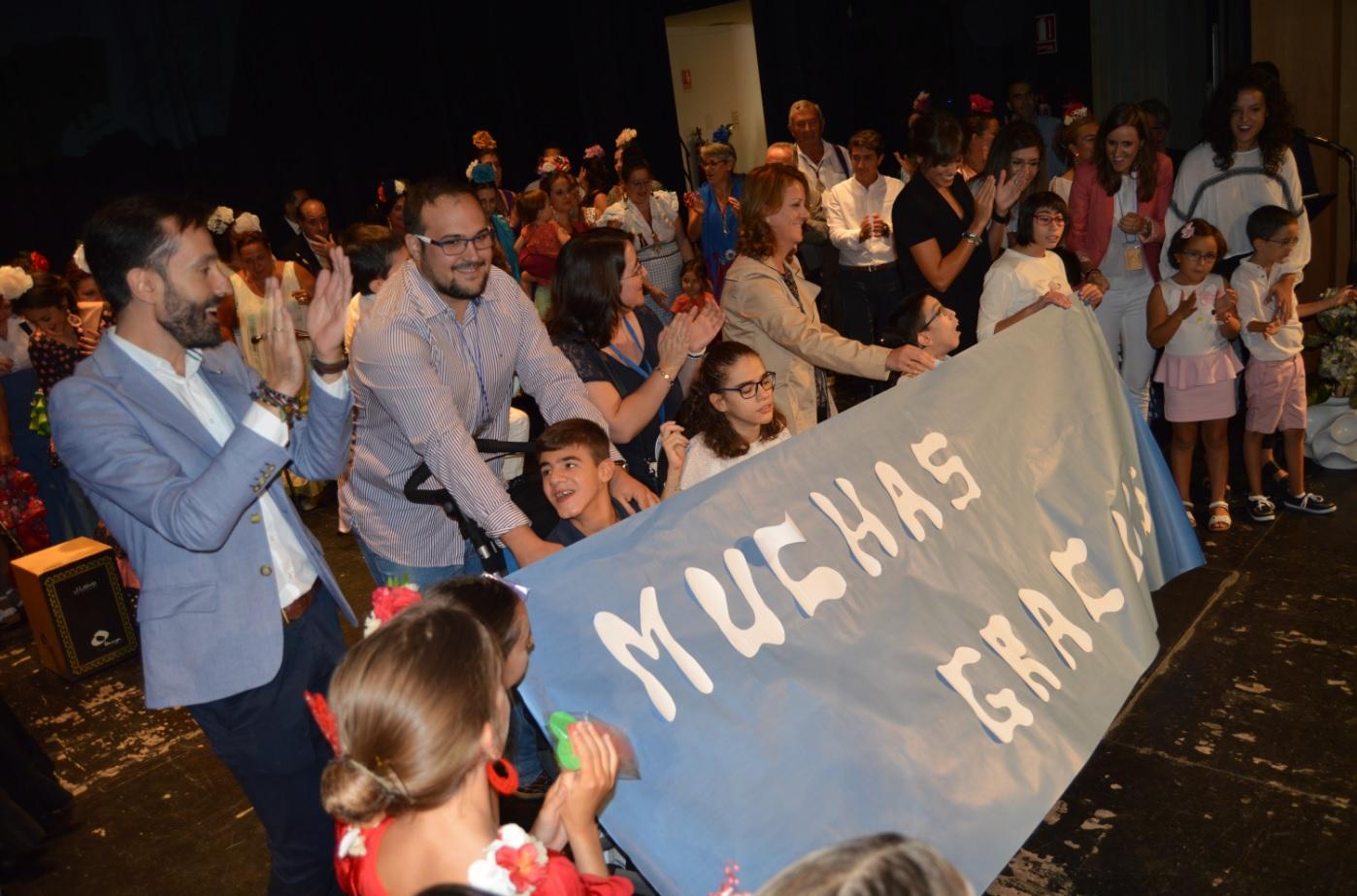 Ninos y niñas de Aspace Jaén portando un gran cartel agradeciendo la participación de todos los grupos.